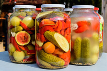 Three Jars With Mixed Pickles On A White Table For Sale At A Food Market With Pickled Cucumbers, Green Tomatoes, Red Peppers, Melon And Cauliflower, Side View With Soft Focus Of Tasty Healthy Food.
