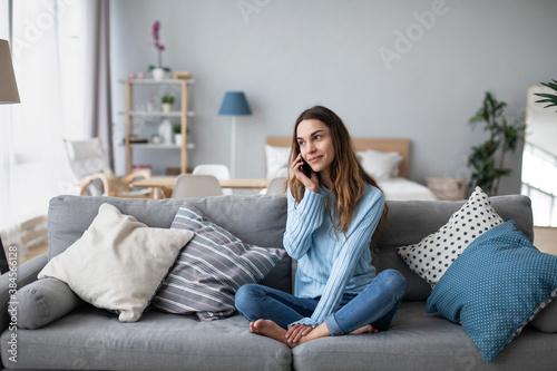 Fototapeta Smiling woman talking to mobile on the sofa. Online conversation. obraz na płótnie