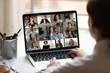 canvas print picture - Rear close up view of female employee brainstorm talk on video call with diverse colleague on laptop. Woman speak engaged in team group discussion, have webcam company online meeting or briefing.