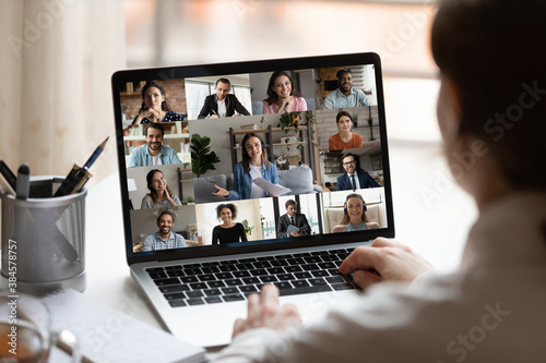 Rear close up view of female employee brainstorm talk on video call with diverse colleague on laptop. Woman speak engaged in team group discussion, have webcam company online meeting or briefing. - 384578757
