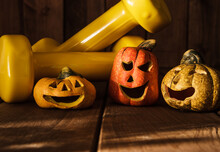 Small Ceramic Halloween Pumpkins With Two Yellow Dumbbells. Healthy Fitness Lifestyle Autumn Composition On Wooden Background.