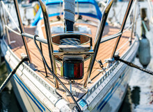 Close Up Of The Bow Of A Sail Boat Moored In A Marina, With Lines, Ropes And Navigational Lantern In Focus.