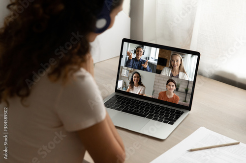 Close up rear view of woman look at laptop screen talk speak on video call with diverse girlfriends at home. Female have webcam digital virtual conference with friends. Online communication concept.