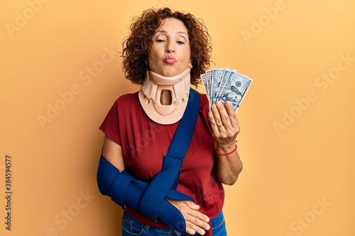 Fototapeta Beautiful middle age mature woman wearing cervical collar and sling holding insurance dollars looking at the camera blowing a kiss being lovely and sexy