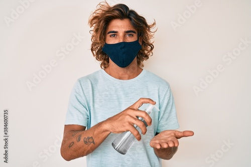 Obraz na plátně Young hispanic man wearing covid-19 mask using hand sanitizer gel looking at the camera blowing a kiss being lovely and sexy