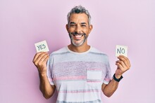 Middle Age Grey-haired Man Holding Yes And No Reminder Smiling With A Happy And Cool Smile On Face. Showing Teeth.