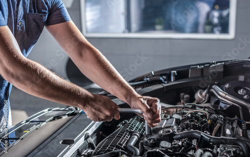 Fotografie, Obraz Auto mechanic working and repair on car engine in mechanics garage