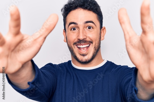 Fototapeta Young hispanic man wearing casual clothes looking at the camera smiling with open arms for hug
