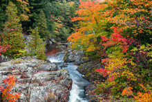 Running Water Of Dead River Through Rocky Terrain In Michigan Upper Peninsula With Colorful Fall Foliage