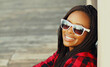 Portrait of happy young smiling african woman wearing a sunglasses in casual over city background