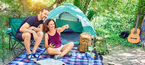 Foto Middle age couple  of hiker smiling happy camping at the forest