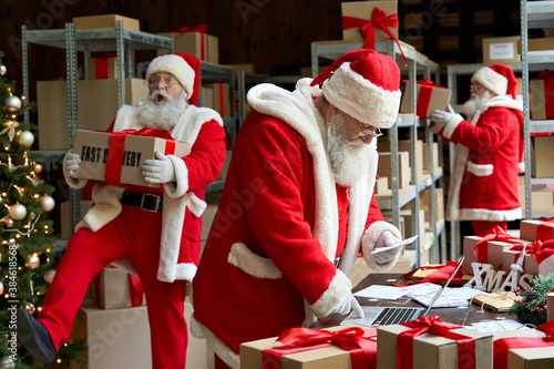 Many busy Santa Clauses packing gift boxes preparing fast xmas delivery Wallpaper Mural