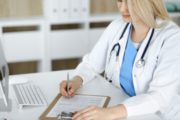 Unknown woman-doctor at work filling up medication history record form in clinic, close-up of clipboard