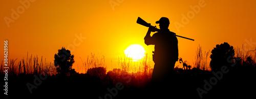 Fotografie, Obraz A silhouette of a male hunter carrying a shotgun