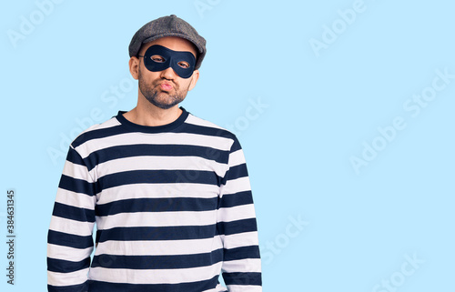 Fototapeta Young handsome man wearing burglar mask looking at the camera blowing a kiss on air being lovely and sexy