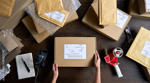 Fotografiet Above table top view of female warehouse worker or seller packing ecommerce shipping order box for dispatching, preparing post courier delivery package, dropshipping shipment service concept