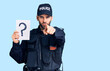 canvas print picture Young handsome man with beard wearing police uniform holding question mark pointing with finger to the camera and to you, confident gesture looking serious