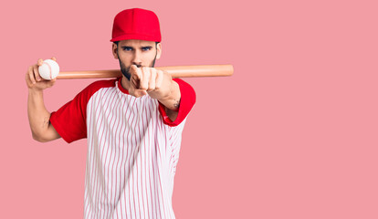 Fototapeta Boks Young handsome man with beard playing baseball holding bat and ball pointing with finger to the camera and to you, confident gesture looking serious