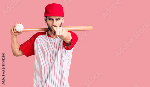 Young handsome man with beard playing baseball holding bat and ball pointing with finger to the camera and to you, confident gesture looking serious