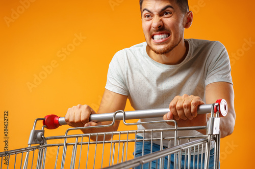 Photo Funny crazy man rushing with shopping trolley to sale