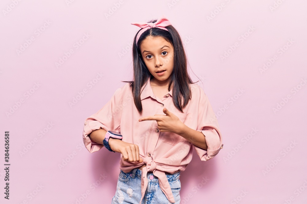 Fototapeta Beautiful child girl wearing casual clothes in hurry pointing to watch time, impatience, upset and angry for deadline delay