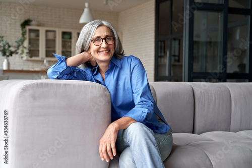 Obraz Happy relaxed mature old adult woman wearing glasses resting sitting on couch at home. Smiling mid age grey-haired elegant senior lady relaxing on comfortable sofa looking at camera. Portrait - fototapety do salonu