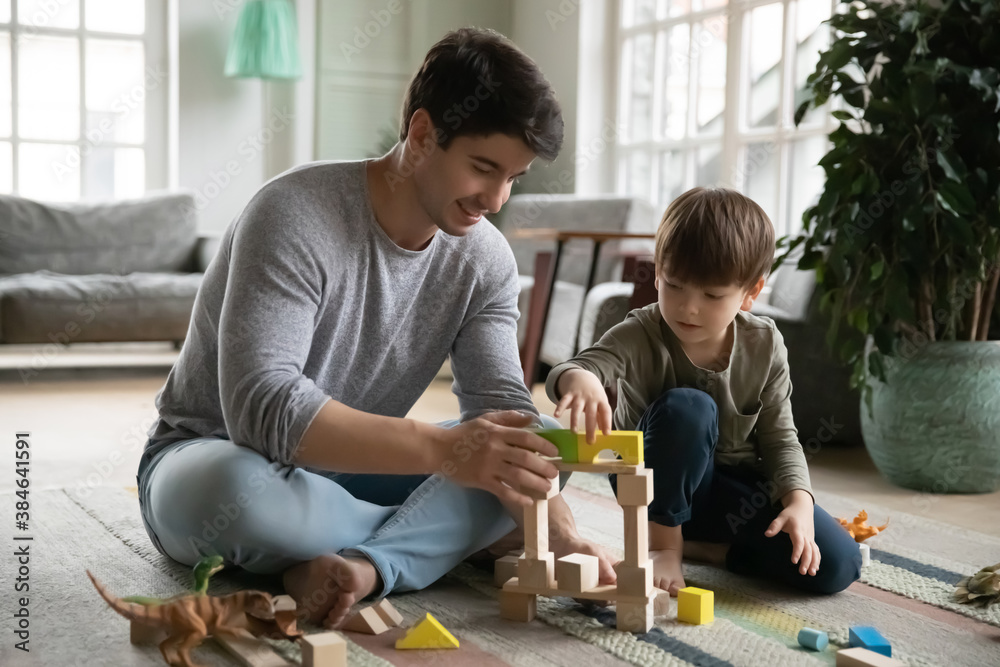 Fototapeta Loving young Caucasian father sit on floor at home play build with bricks with little son. Happy caring dad and small preschooler boy child have fun engaged in game activity in living room together.