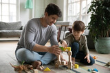 Loving young Caucasian father sit on floor at home play build with bricks with little son. Happy caring dad and small preschooler boy child have fun engaged in game activity in living room together.