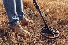 Man With Metal Detector Equipment Searching For Metal Goods In The Field