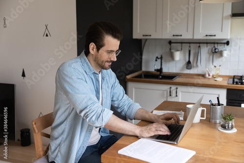 Side view happy smart young man in eyewear looking at laptop screen, involved in online communication. Smiling millennial businessman working distantly web surfing at home office, freelance concept. - 384646596