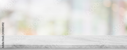 Obraz Empty white marble stone table top and blur glass window interior cafe and restaurant banner mock up abstract background - can used for display or montage your products. - fototapety do salonu
