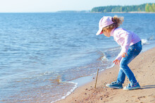 Little Girl Playing On The Seashore In The Sand. Volunteer Child Cleaning Up Rubbish Trash, Garbage On The Beach. Natural Education Of Children. Copy Space, Place For Text