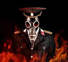 Photo Of A Post Apocalyptic Military Officer In Uniform Suit And Peaked Cap Standing In Soviet Gas Mask In Fire.