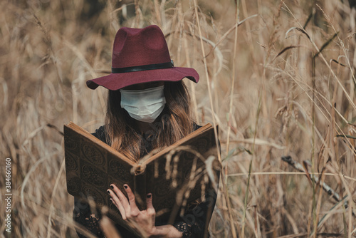 Tablou Canvas Young enchantress casting a spell in the forest, wearing a mask