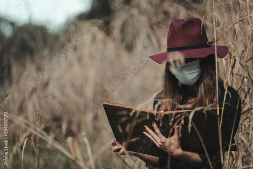 Canvas Print Young enchantress casting a spell in the forest, wearing a mask