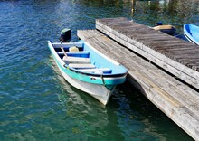 A Small Boat Is Moored To A Wo...
