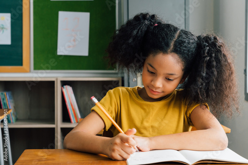 African American school girl sitting in school writing in note book with pencil, studying, education, learning. Female student at desk in classroom in exam.