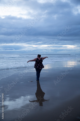 Woman pirouettes gracefully on the beach after sunset Fototapeta