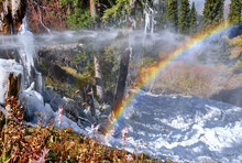 Rainbow Near The Waterfall In The Middle Of The Forest In The Highlands; Massive Icicles Made Of Dripping Ice On Spruce Branches