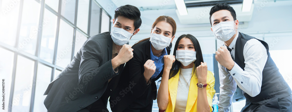 Fototapeta portrait of young asian businessman and businesswoman wearing corona virus face mask  hand rise empower hand gesture successful achievement concept