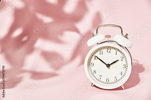 White alarm clock and leaves shadows on pastel pink background