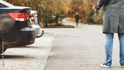 Fotografía man walking to their parked car after stroll in autumn park