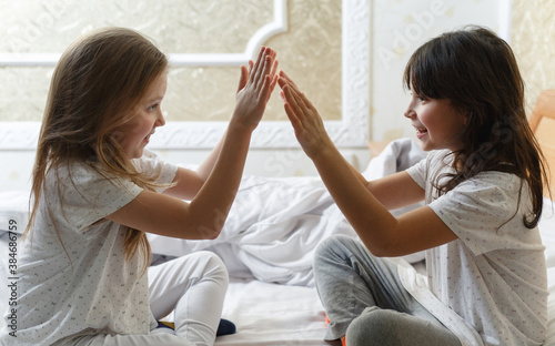 sisters playing in the bedroom on the bed Wallpaper Mural