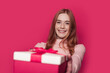 Leinwandbild Motiv Charming ginger woman with freckles is giving a present at the camera smiling on a pink wall at studio