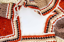 Crocheted Blanket Of Autumn Colors On A White Background, Located Along The Edge. View From Above.