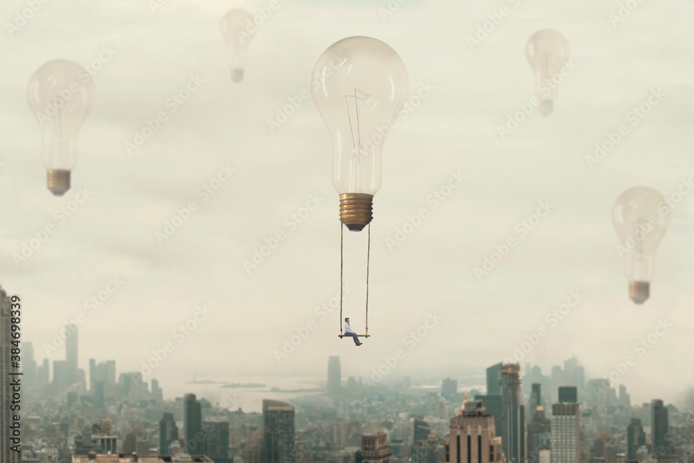 Fototapeta surreal moment of a woman traveling on a swing carried by a light bulb over a metropolis
