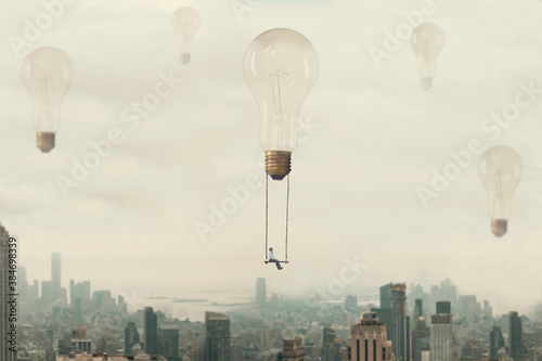 Obraz surreal moment of a woman traveling on a swing carried by a light bulb over a metropolis - fototapety do salonu