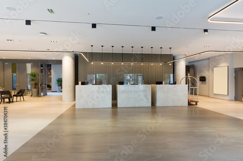 Fototapeta Interior of a hotel lobby with reception desks with transparent coronavirus guar