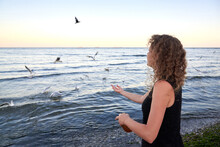 A Woman Feeds Seagulls With Br...