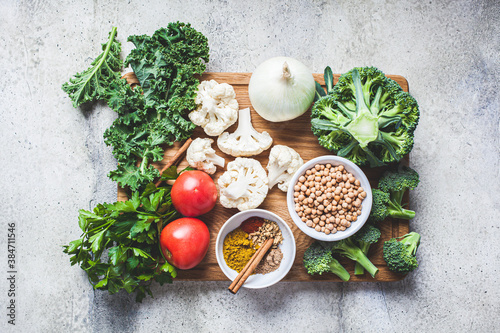Cooking background of fresh vegetables, spices and beans. Raw ingredients for cooking vegetarian curry with vegetables and chickpeas on a wooden board, top view.